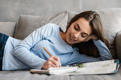 Portrait of a pretty young woman studying. While laying with notebook on a couch at home Royalty Free Stock Photography