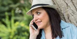 Portrait of pretty young woman talking on mobile phone. Outdoors Royalty Free Stock Photo