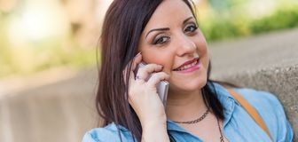 Portrait of pretty young woman talking on mobile phone. Outdoors Stock Photography