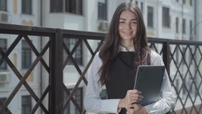 Portrait of a pretty young woman on the terrace looking in the camera holding laptop in hands. Businesswoman spending. Portrait of a pretty young woman on stock footage
