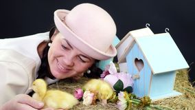 Portrait, a pretty young woman with two pigtails and in a funny pink hat playing with small yellow ducklings. In the. Background a haystack, colored birdhouses stock video footage