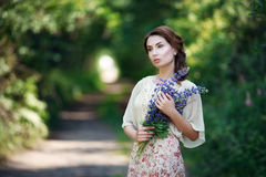 Portrait of pretty young woman walking in a fairy forest with bouquet of flowers. Royalty Free Stock Photo