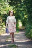 Portrait of pretty young woman walking in a fairy forest with bouquet of flowers. Royalty Free Stock Photos