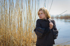 Portrait of a pretty young woman walking outdoors near lake with reed. Portrait of a pretty young woman walking outdoors near a lake with reed in their hands Royalty Free Stock Photography