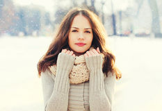 Portrait pretty young woman wearing a knitted sweater and scarf in winter over snowflakes Stock Images
