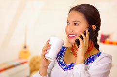 Portrait pretty young woman wearing traditional andean blouse, holding white coffee mug and talking on mobile phone Stock Photography