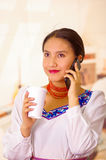 Portrait pretty young woman wearing traditional andean blouse, holding white coffee mug and talking on mobile phone Royalty Free Stock Images