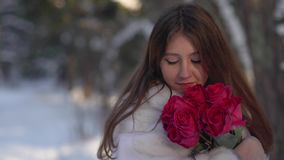 Portrait of pretty young woman in winter forest holding the flowers and inhale smell stock footage