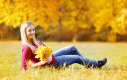 Portrait pretty young woman with yellow maple leafs outdoors in Stock Images