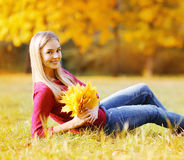 Portrait of pretty young woman with yellow maple leafs Royalty Free Stock Photos