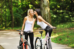 Portrait of pretty young women with bicycle in a park Royalty Free Stock Image