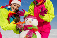 Portrait of a pretty young women with a snowman Stock Photos