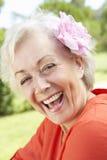 Portrait principal et d'épaules de femme supérieure de sourire avec la fleur dans les cheveux Photographie stock libre de droits