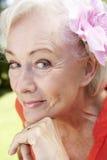 Portrait principal et d'épaules de femme supérieure de sourire avec la fleur dans les cheveux Image stock