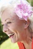 Portrait principal et d'épaules de femme supérieure de sourire avec la fleur dans les cheveux Photo libre de droits