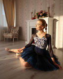 Portrait of a professional ballet dancer sitting on the wooden floor. Ballet concept. Royalty Free Stock Photography