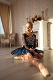 Portrait of a professional ballet dancer sitting on the wooden floor. Female ballerina having a rest. Ballet concept. Royalty Free Stock Photo