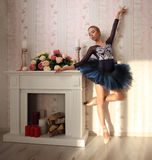 Portrait of a professional ballet dancer in sun light in home interior, standing on one leg. Ballet concept. Stock Photography