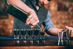 Portrait of professional barman pouring alcoholic in shot glasses at bar. Portrait of professional barman pouring alcoholic digestif in shot glasses at bar Stock Photography