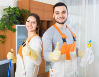 Portrait of professional cleaners. Portrait of smiling professional cleaners team with equipment at client house Stock Photography