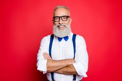 Portrait of professional, cool, old man with beaming smile having his arms crossed, looking at camera, wearing blue bow-tie and s royalty free stock photo