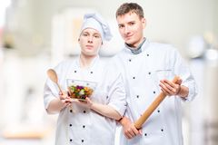 Portrait of professional couple of cooks with salad and rolling pin. On the background of commercial kitchen royalty free stock photos