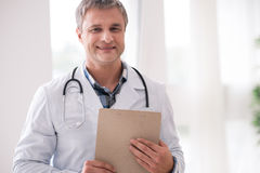 Portrait of professional doctor that enjoying his job. Visit my consultation. Attractive male person keeping smile on his face and holding holder in both hands royalty free stock photography