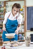 Portrait of Professional Female Ceramist in Apron Glazing Cerami. C Bowl on Turntable in Workshop. Vertical Image Royalty Free Stock Image