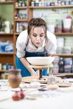 Portrait of Professional Female Ceramist in Apron Glazing Cerami. C Bowl on Turntable in Workshop. Blowing Flour Dust from Surface.Vertical Image Orientation Royalty Free Stock Photos