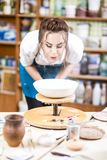 Portrait of Professional Female Ceramist in Apron Glazing Ceramics. Portrait of Professional Female Ceramist in Apron Glazing Ceramic Bowl on Turntable in Stock Photo