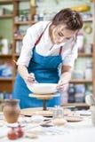 Portrait of Professional Female Ceramist in Apron Glazing Ceramics. Portrait of Professional Female Ceramist in Apron Glazing Ceramic Bowl on Turntable in Stock Image