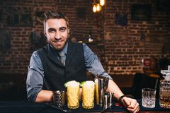 Portrait of professional handsome barman smiling at camera, preparing cocktails and serving fresh drinks royalty free stock images