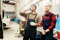 Young Auto Technicians At Work. Portrait of professional handsome male car mechanics in workwear standing in repair shop and looking at truck thoughtfully Stock Photos