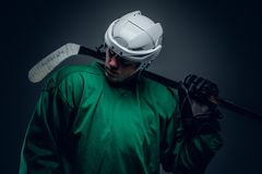 Hockey player holds gaming stick. Portrait of professional hockey player holds gaming stick isolated on grey background stock images