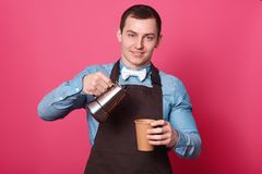 Portrait of professional male barista pours aromatic coffee into paper cup, wears blue shirt, white bow tie and brown apron, royalty free stock photography