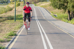 Portrait of Professional Male Cyclist Doing Uphill on Road Bike. Cycling Ideas. Portrait of Professional Male Cyclist Doing Uphill on Road Bike. Fully Equipped Stock Image