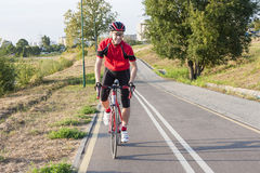 Portrait of Professional Male Cyclist Doing Uphill. Sport and Cycling Ideas. Portrait of Professional Male Cyclist Doing Uphill Out of the Saddle on Road Bike Stock Photos