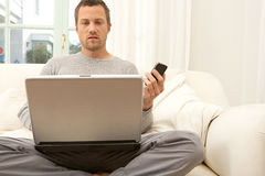 Portrait of professional man with laptop and smart phone at home. Stock Image