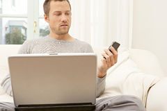 Portrait of professional man with laptop and smart phone at home. Stock Photo