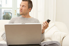 Portrait of professional man with laptop and smart phone at home. Stock Photography