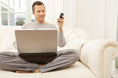 Portrait of professional man with laptop and smart phone at home. Royalty Free Stock Images