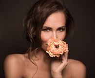 Portrait of professional model girl with orange rose. Close-up portrait of professional model girl smiling  on dark. Beautiful lady with brown hair looking at Stock Images
