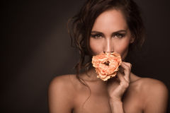 Portrait of professional model girl with orange rose. Fashion and vogue concepts. Portrait of professional fashion model girl smiling for the camera while Stock Photos