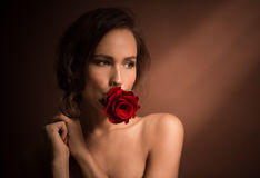 Portrait of professional model girl with red rose. Rose and kiss concepts. Portrait of professional model girl with red rose in her mouth. Beautiful lady posing Royalty Free Stock Image