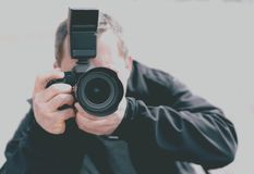 Portrait of a professional photographer. With a camera pointed toward the subject stock photography