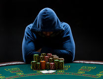 Portrait of a professional poker player sitting at pokers table Royalty Free Stock Photography