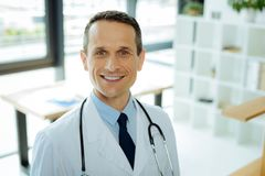 Portrait of a professional skillful doctor. At the hospital. Portrait of a professional skillful handsome doctor wearing a labcoat and smiling while being at Royalty Free Stock Image