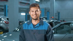 Portrait of Professional smiling car mechanic working in modern auto repair service stock video footage