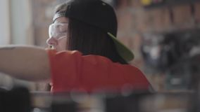 Portrait professional woman in a cap and protective glasses with pierced lip and ring in nose measuring length of the. Young woman in black cap and protective stock video