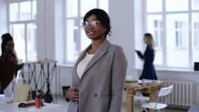 Portrait of professional young African entrepreneur business woman in eyeglasses posing at modern light loft office. Positive black female corporate manager in stock video